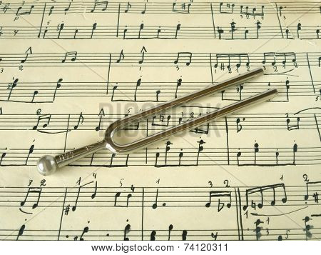 Fork on old sheet music, closeup