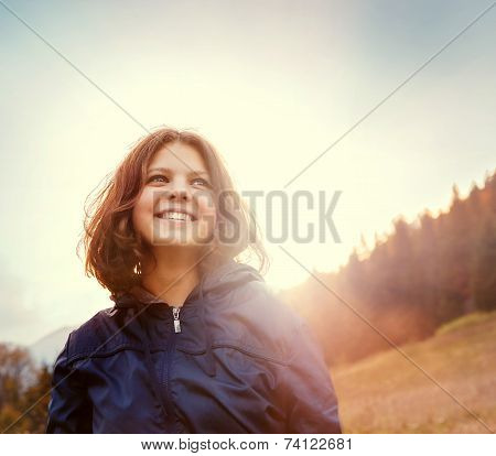 Happy Smiling Young Woman In Sunset Light On The Mountain Hill