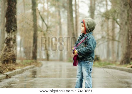 Boy Plays The Guitar In Rainy Park