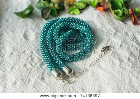 Necklace From Beads Of Color Aquamarine On A Textile Background