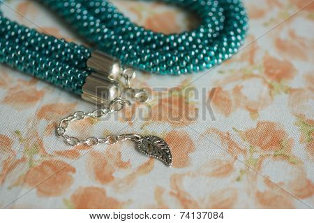 Green-blue Necklace From Beads Against A Flower Print