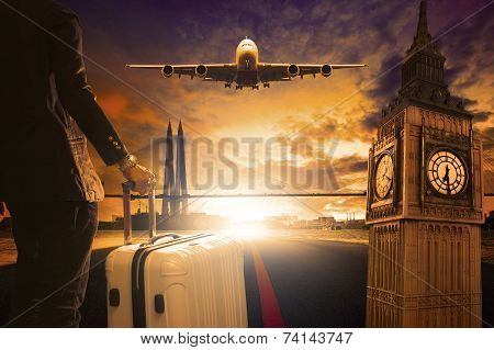 Young Business Man Standing With Luggage On Urban Airport Runway And Jet Plane Flying Above Against