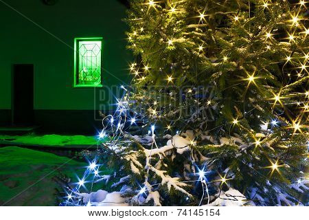 Christmas And  New Year Fir Tree  Night With Illumination  Lights And Rural House