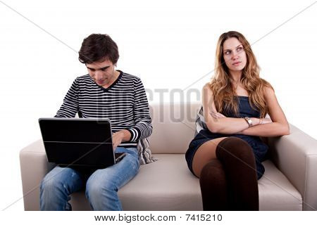 Couple Sitting On The Couch, He Playing Computer And She Look To Other Way Bored