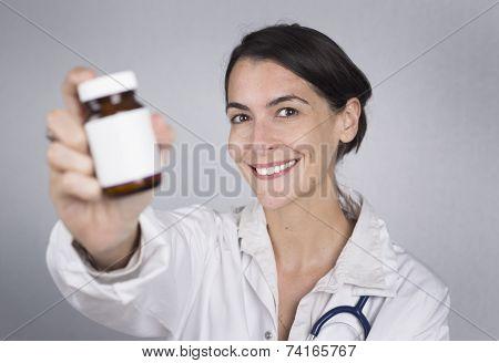 Smiling Female Doctor Holding A Bottle Of Tablets