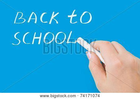 Hand with chalk writing Back to school on blackboard