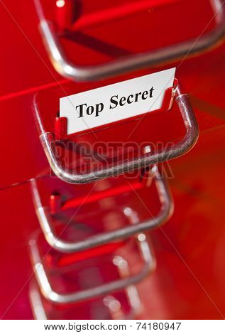 Red file cabinet with card Top Secret - business background