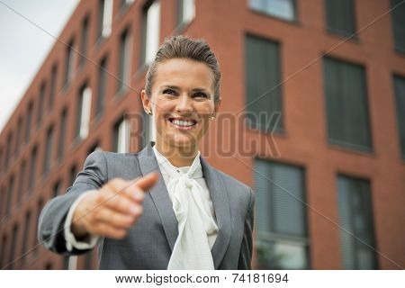 Portrait Of Happy Business Woman Stretching Hand For Handshake In Front Of Office Building