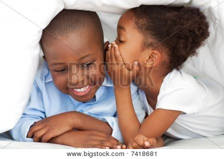 Ethnic Little Girl Whispering Something To Her Brother