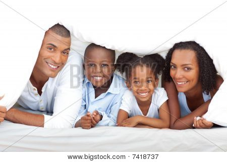 Merry Family Having Fun Lying Down On Bed