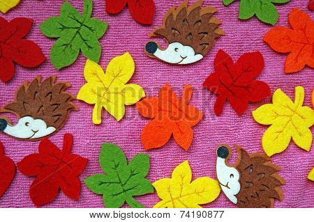 Hedgehogs And Colorful Maple Leaves Out Of Felt On A Pink Fabric As A Background