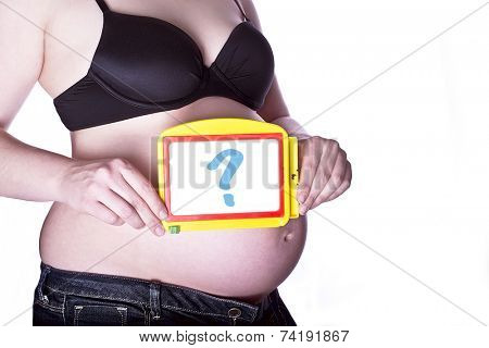 pregnant woman clothed in black bra and jeans holding a toy slate with a questionmark in front of her belly