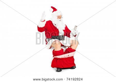 Santa looking at an empty toilet paper roll seated on a toilet isolated on white background