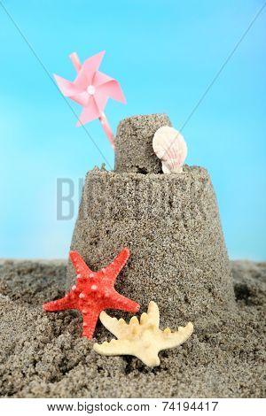 Sandcastle with pinwheel on sandy beach