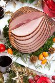 stock photo of kumquat  - Christmas dinning table with glazed roasted ham with tomatoes herbs and kumquats - JPG