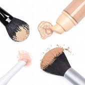stock photo of foundation  - Closeup concealer pencil foundation with open jar loose cosmetic powder and makeup brushes on white background - JPG