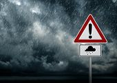 stock photo of sleet  - A dark cloudy sky with rain and warning sign  - JPG