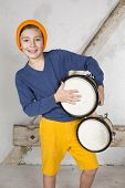 picture of drums  - a young boy playing the drum and smiling - JPG