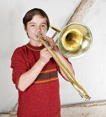 stock photo of trombone  - portrait of a boy playing the trombone - JPG