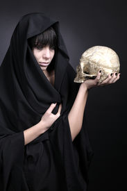 picture of cranium  - Woman holding a human cranium. Covered with black cloth. Studio shot. Black background