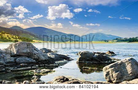 Lake With Boulders In Mountains At Sunrise