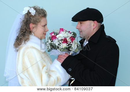 Young bride and groom posing for the camera outside