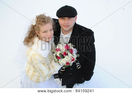 Young bride and groom posing in the snow
