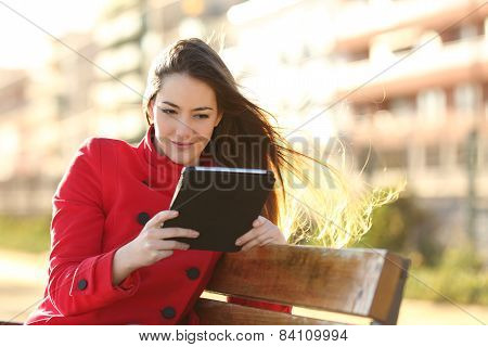 Woman Reading An Ebook Or Tablet In An Urban Park