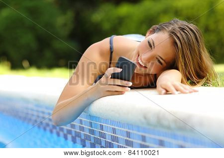 Woman Using A Smart Phone In A Poolside In Summer
