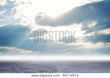 Concrete floor on background of clouds, sun