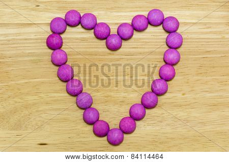 Sugar Coated Candy Heart on Wooden Background