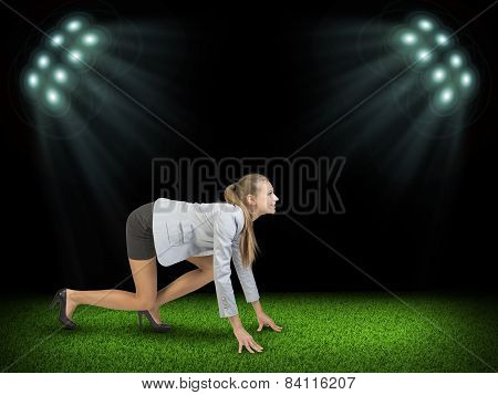 Woman begins to start. Green grass and black sky with rays of searchlights