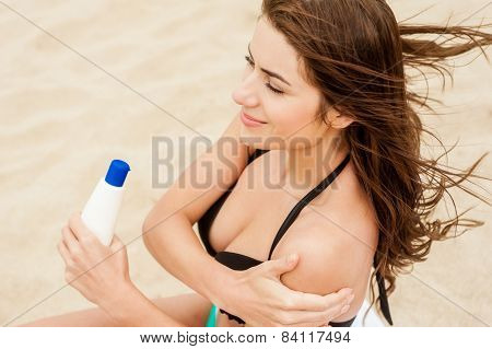 Woman is applying sunblock
