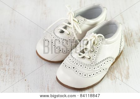 White Baby Shoes On White Wooden Background
