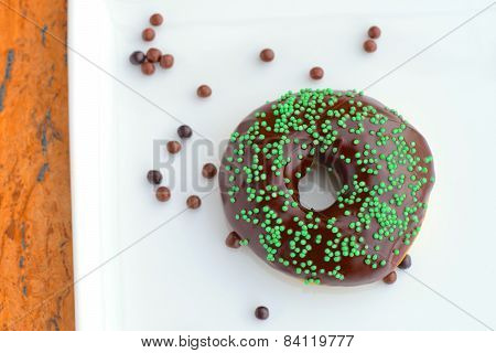 Donuts with glazed chocolate and green sprinkle sugar