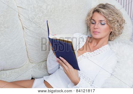 beautiful woman reading book at bedroom