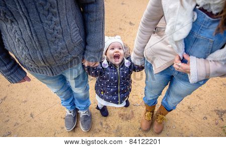 Man and woman holding hands of happiness little girl