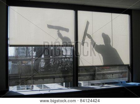 Window washers in silhouette
