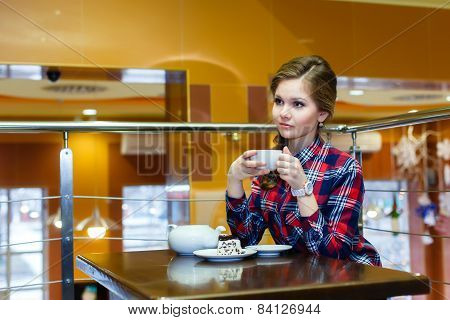 Young Nice Women In A Plaid Shirt Drinking Tea In A Cafe