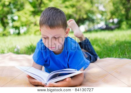 Boy Lying On Beach Mat And Reading Book