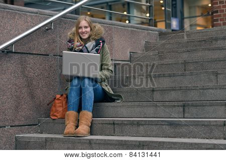 Pretty Young Woman Sitting On Steps In Town