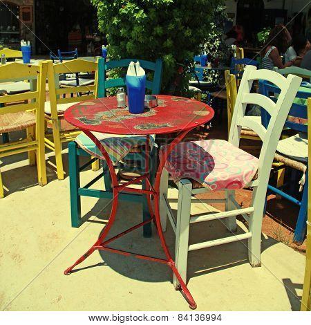 Outdoor Restaurant With Multicolored Furniture (crete, Greece )