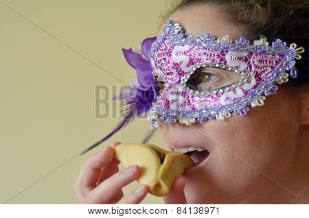 Woman Eat Hamantaschen Cookie And Wearing Purim Mask