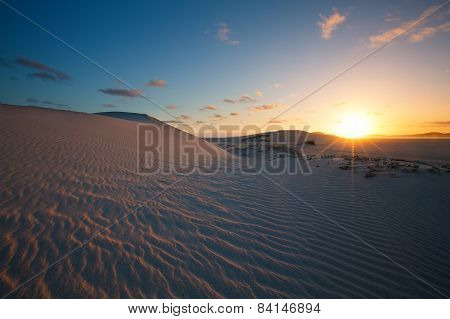 Glorious Sunset Over Rippled Sand Dune Next To A Lagoon