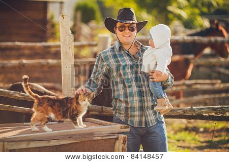 Young father with his little daughter in his arms, in the summer in the countryside.
