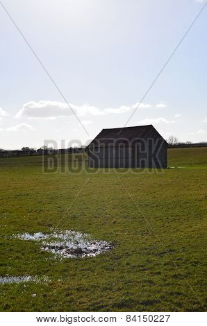 Flint barn in farm field.