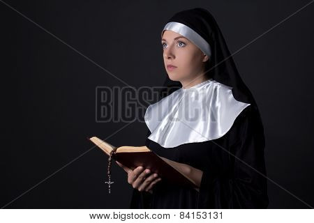 Religion Concept - Young Beautiful Woman Nun Reading Bible Over Grey
