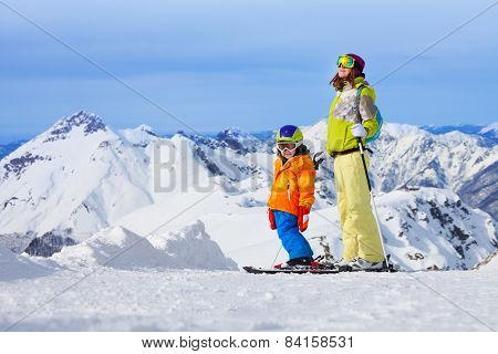 Ski vacation in mountains, woman and child happy