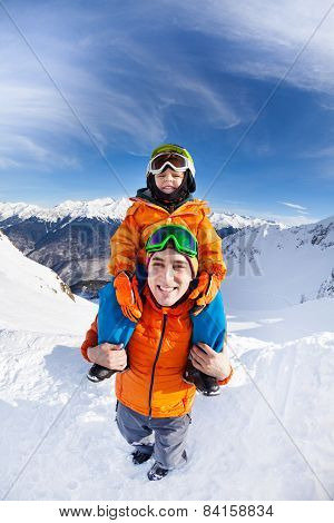 Little boy sit on fathers shoulders in mountains