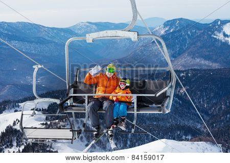 Man skier with child lift on ropeway chair
